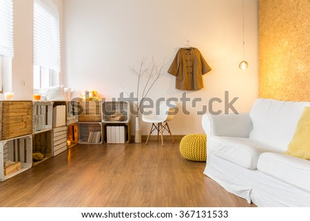 Spacious living room with wooden floor and comfortable white couch. Next to it wooden shelves with decorations. - stock photo