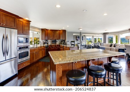 Spacious luxury kitchen room interior with kitchen island and black stools. - stock photo