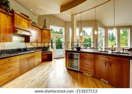Spacious luxury kitchen room with round kitchen island and steel appliances - stock photo