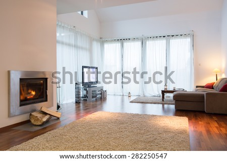 Spacious modern cozy living room with fireplace - stock photo