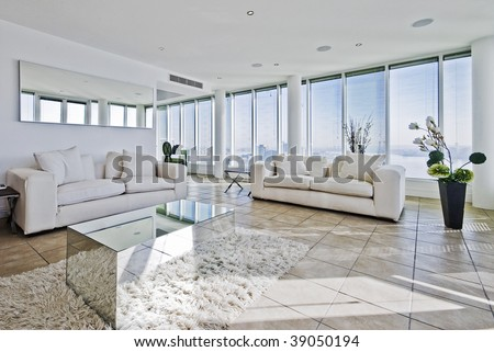 spacious penthouse living room with floor to ceiling windows and modern furniture - stock photo