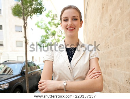 Spacious portrait of an attractive young executive business woman wearing stylish professional clothing in a city street, smiling with crossed arms outdoors. Business people and lifestyle. - stock photo