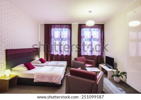 Spacious, violet hotel room with two single beds - stock photo