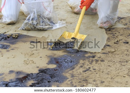 Spade excavate in dirty beach as tool to scoop crude oil on clean-up operation from crude oil spilled into Ao Prao Beach on July 31, 2013 in Rayong province, Thailand. - stock photo