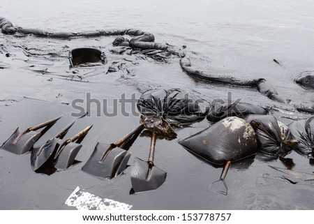 Spades, Absorbent paper, Oil Containment boom and Plastic Bags are some tools for the clean up operation on oil spill accident on Ao Prao Beach at Samet island on July 2013 in Rayong, Thailand. - stock photo