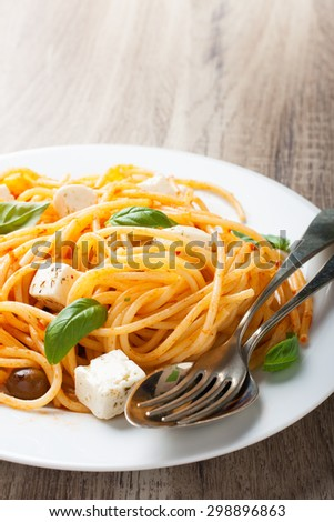 Spaghetti al pomodoro, one of the simplest Italian rustic dishes with the pasta tossed in a sauce of tomato, basil, garlic and a little sugar and oil. - stock photo