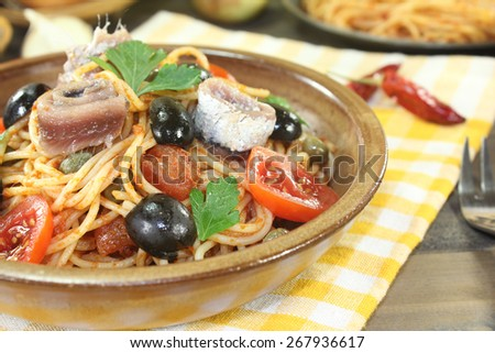 Spaghetti alla puttanesca with olives and tomatoes on a napkin - stock photo