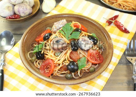 Spaghetti alla puttanesca with olives, capers and anchovies on a napkin - stock photo