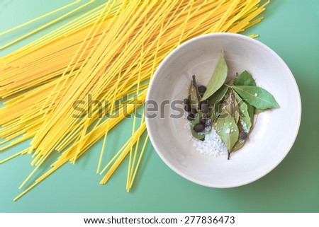 Spaghetti and bowl with bay leaves, pepper and sea salt on green background - stock photo