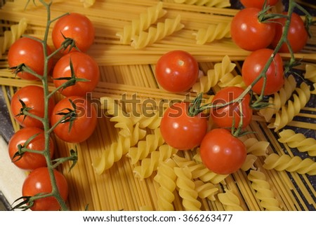 Spaghetti and macaroni on the kitchen table with small cherry tomatoes and avocado vegetable ready to be cooked  - stock photo