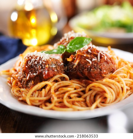 spaghetti and meatballs at cluttered dinner table - stock photo