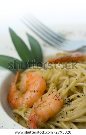 Spaghetti and prawns in cream sauce, herb garnish. Served on deep white, round bowl with wide rim sprinkled with ground pepper. Portrait, macro, shallow depth of field, fade to white background. - stock photo