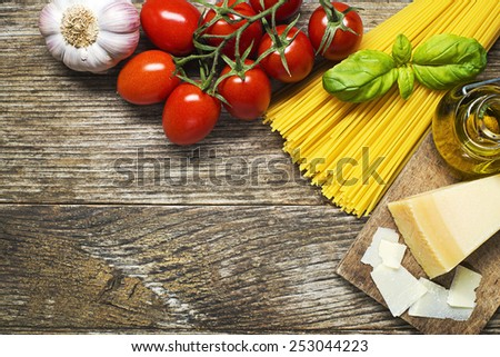 Spaghetti and tomatoes with parmesan cheese on wooden background - stock photo
