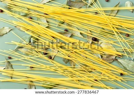 Spaghetti, bay leaves and pepper on green background - stock photo