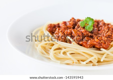 Spaghetti bolognese decorated with coriander leaf on a white plate and on white background - stock photo