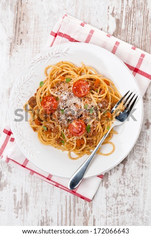 spaghetti bolognese on a plate on wooden table, top view, vertical - stock photo