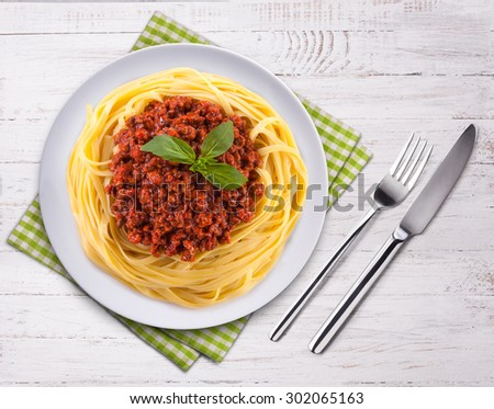 Spaghetti bolognese on the wooden table. Top view. Fork, knife and towel. - stock photo