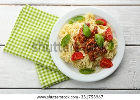 Spaghetti Bolognese on white plate, on color wooden background - stock photo