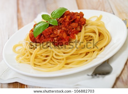 Spaghetti Bolognese on white plate on wooden table - stock photo