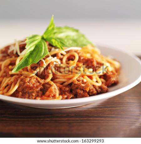 spaghetti bolognese with basil garnish - stock photo