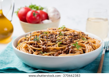 Spaghetti bolognese with cheese and basil on a plate Italian ingredients background - stock photo