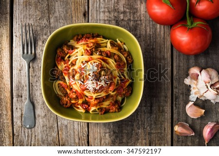 Spaghetti bolognese with parmesan cheese on rustic table - stock photo