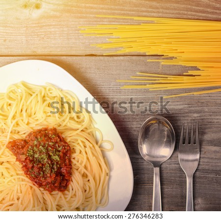 Spaghetti bolognese with  tomato beef sauce and raw pasta on wooden background - stock photo