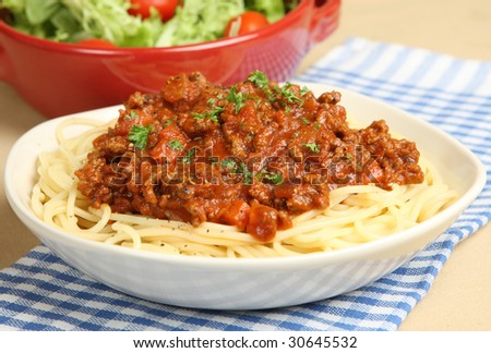 Spaghetti bolognese with tomato salad - stock photo