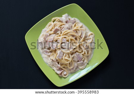 Spaghetti Carbonara with bacon and cheese, top view on black background - stock photo