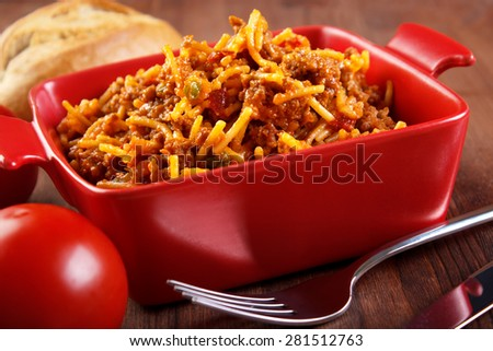 Spaghetti casserole homemade food , served from small red ceramic oven pan - stock photo