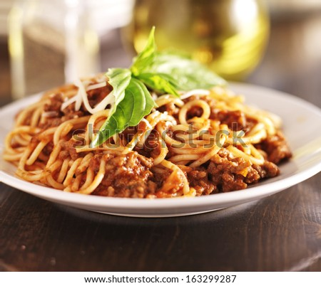 spaghetti dinner with meat sauce and basil close up - stock photo