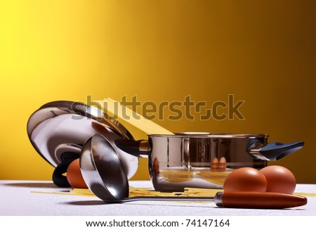 spaghetti, eggs, cheese and utensils on table - stock photo