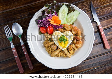 Spaghetti Fried Egg with seafood on old wood - stock photo