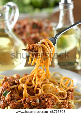 spaghetti hanging on a fork at dinner - stock photo