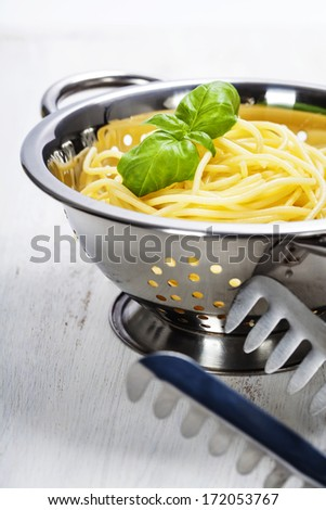 spaghetti in colander over white - stock photo