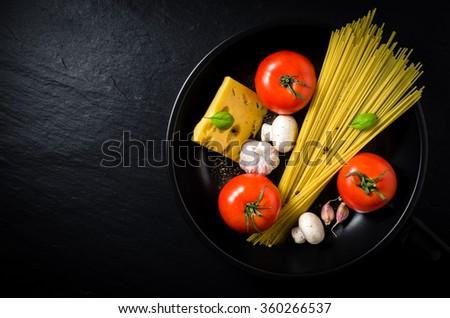 Spaghetti ingredients in black frying pan - stock photo