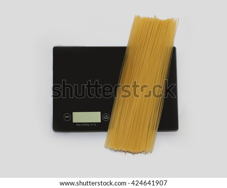 Spaghetti on a digital white kitchen scale. (weighing products) - stock photo