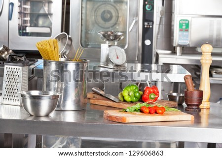 Spaghetti pasta in container and bell peppers on cutting board at commercial kitchen - stock photo