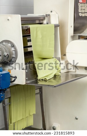 Spaghetti pasta sheet being processed in machine at commercial kitchen - stock photo