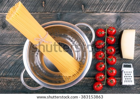 Spaghetti pasta, tomatoes, cheese, colander and grater on old rustic background. Ingredients for cooking pasta. Top view - stock photo