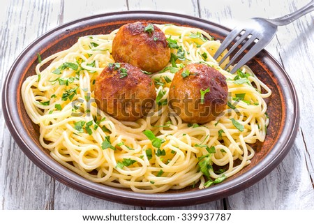 Spaghetti pasta with meatballs sprinkled with chopped parsley on the dish on the old white wooden table, view from above - stock photo