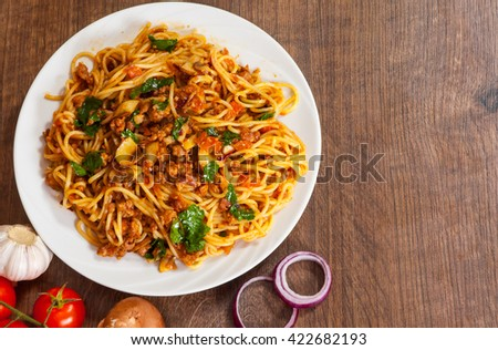 spaghetti pasta with mushroom, vegetables and minced meat in a plate on wooden table - stock photo