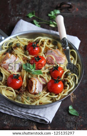 Spaghetti pasta with roasted cherry tomatoes, bacon slices, capers and herbs in a pan ready to serve - stock photo
