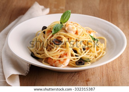 spaghetti pasta with shrimps and sweet basil on wooden table - stock photo