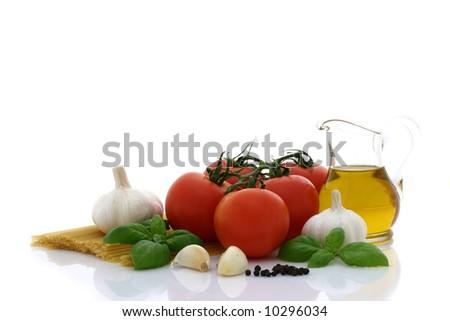 Spaghetti preparation: tomatoes, olive oil, garlic and basil - stock photo