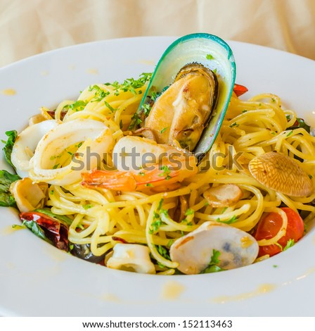 Spaghetti seafood in white dish on the stone table - stock photo