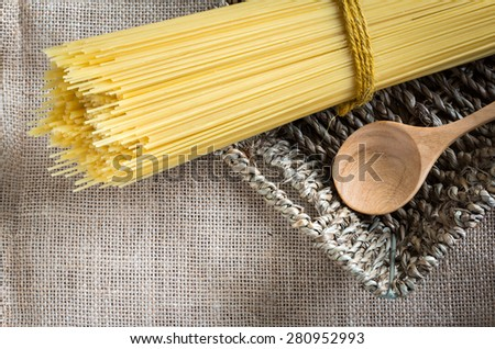 spaghetti uncooked and spoon wood in basket on gunny - stock photo