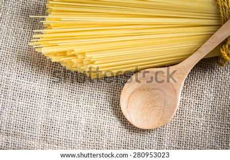 spaghetti uncooked and spoon wood on gunny - stock photo