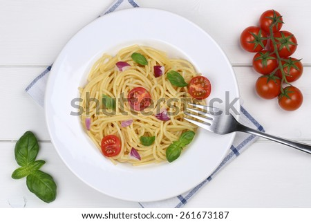 Spaghetti with basil and tomatoes noodles pasta meal from above on a plate - stock photo