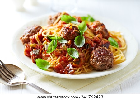 Spaghetti with beef meatballs and fresh basil leaves - stock photo